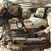 Soldiers investigate beyond the bullet holes after attacks.