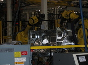 Two quality control robots take digital photos of a GM vehicle part. Technicians will later examine the photos. The body shop section of GM Lansing Delta is the worksite of some 1,200 robots that work alongside warm-blooded technicians. GM began using robots in its body shops more than 10 years ago.
