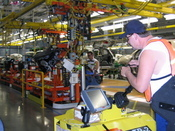 A wireless order system on a plant truck tells a GM employee the parts he needs to retrieve. A 22 Mbyte per second wireless network runs throughout the plant.