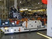 An automated cart carries an entire vehicle chassis to the assembly line.